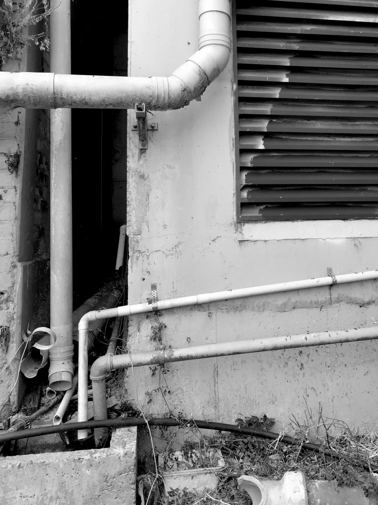 A black and white photograph of a worn wall with pipes and a vent
