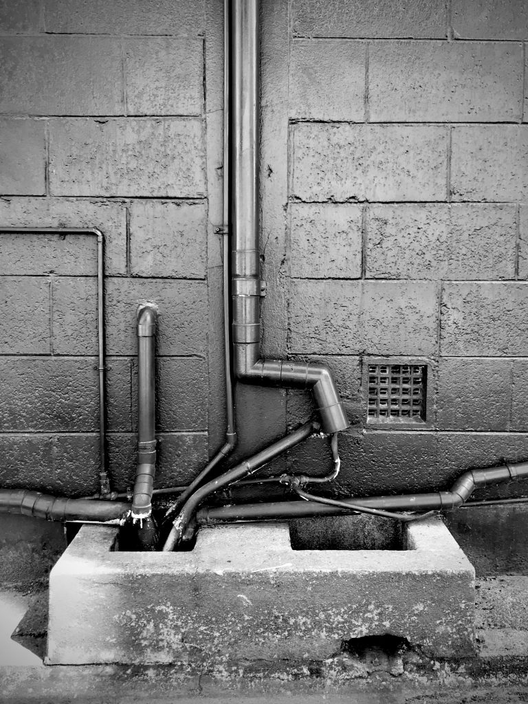 A black and white photograph of pipes running into a drain