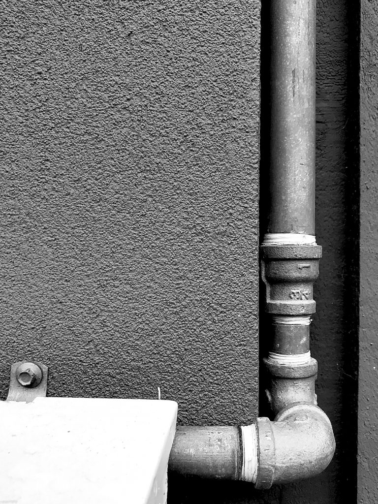 A black and white photograph of a concrete wall and drain pipe