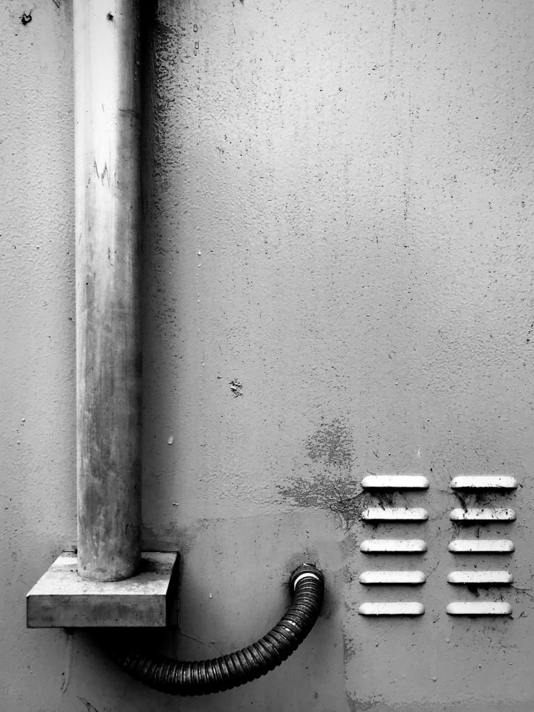 A black and white photograph of a single drain pipe and vents