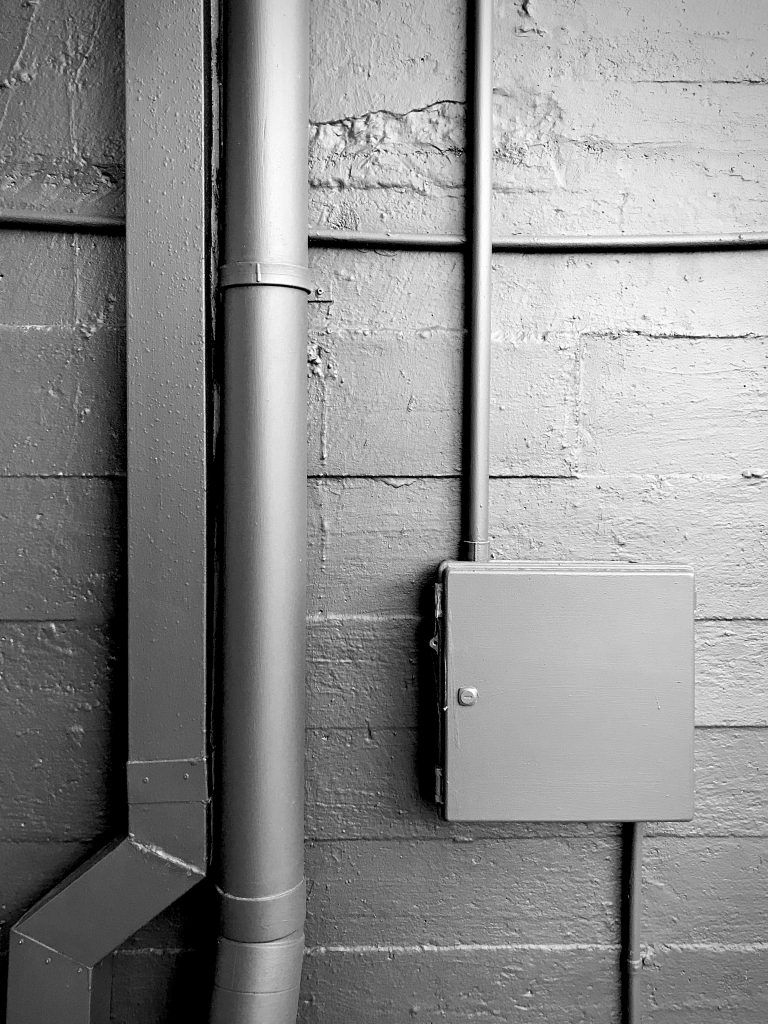 A black and white photograph of a power box fixture and drain pipes on a dark wall