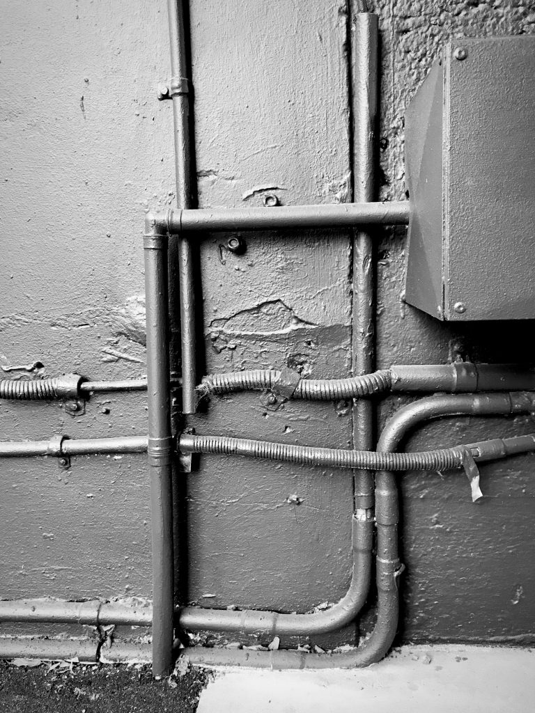 A black and white photograph of a group of pipes running across a wall, the pipes and the wall have been painted in a dark tone.