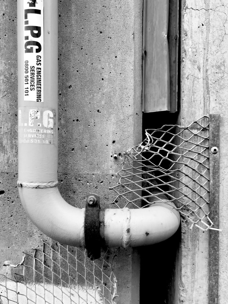 A black and white photograph of a pipe emerging from a wall with a metal grill surrounding it.