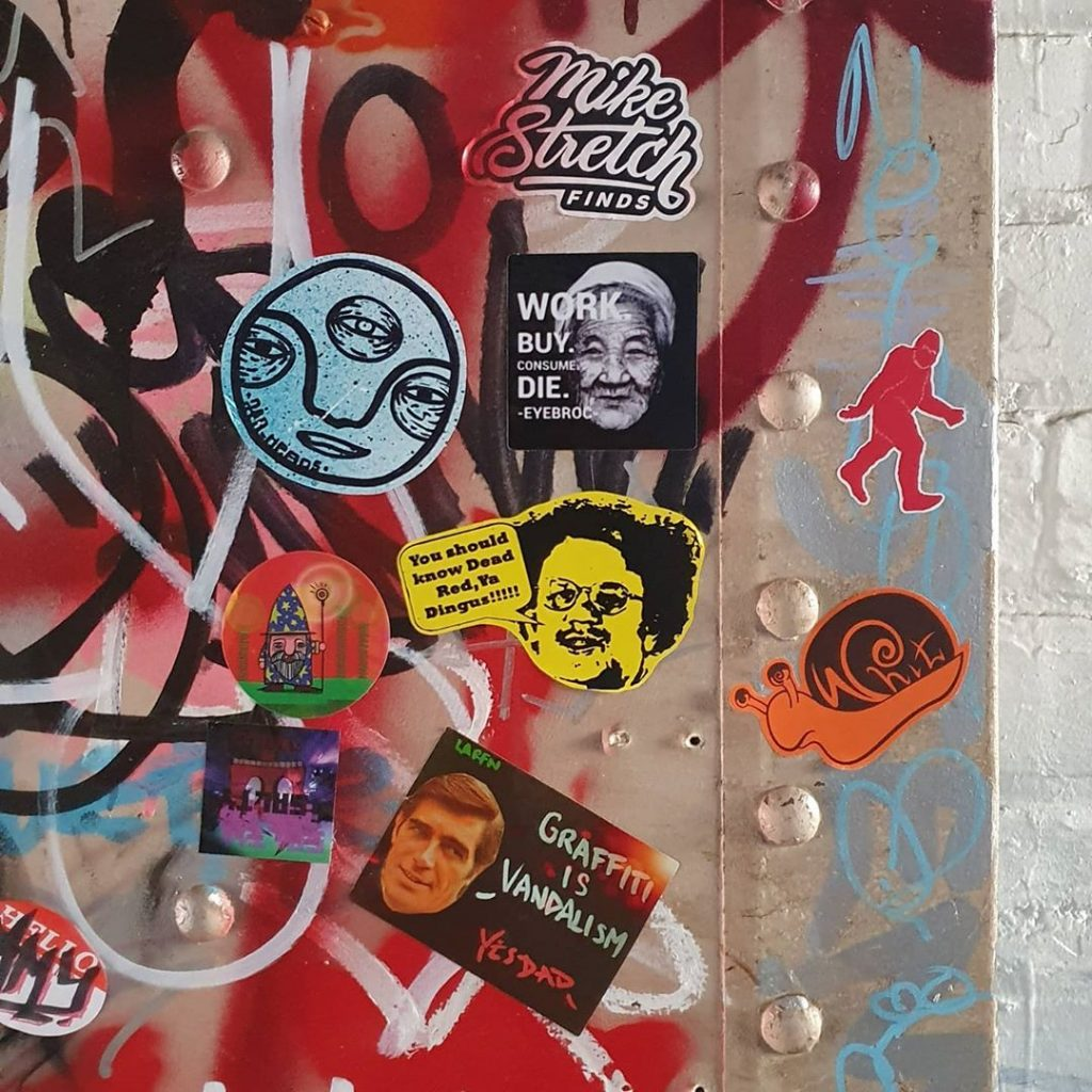 Stickers on a graffitied wall in Dunedin
