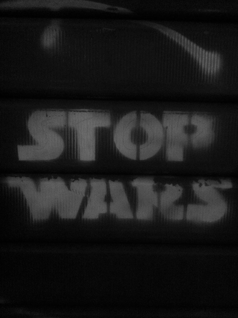 The words Stop Wars is stencilled in the style of the Star Wars logo