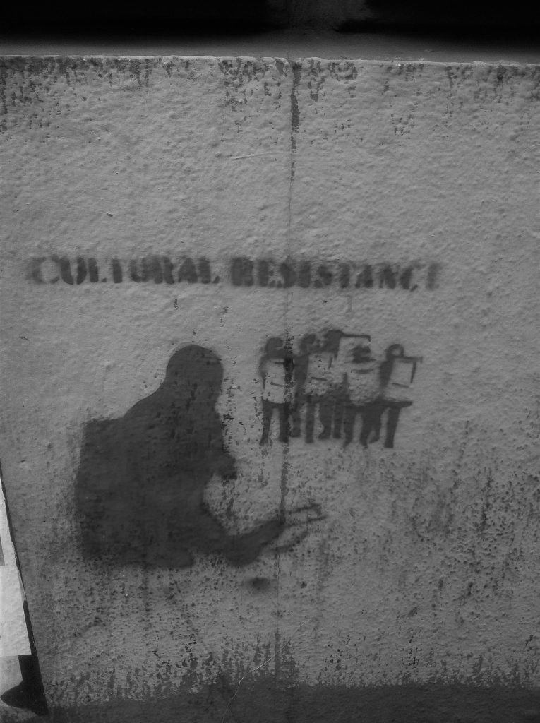 A crowd of protestors are stencilled on a wall under the words Cultural Resistance