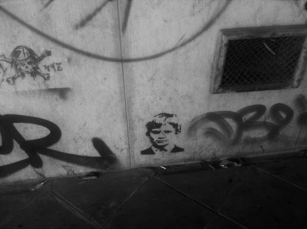 A graffitied wall featuring stencils, one of which is a skull and cross bones, the other a portrait of a young boy