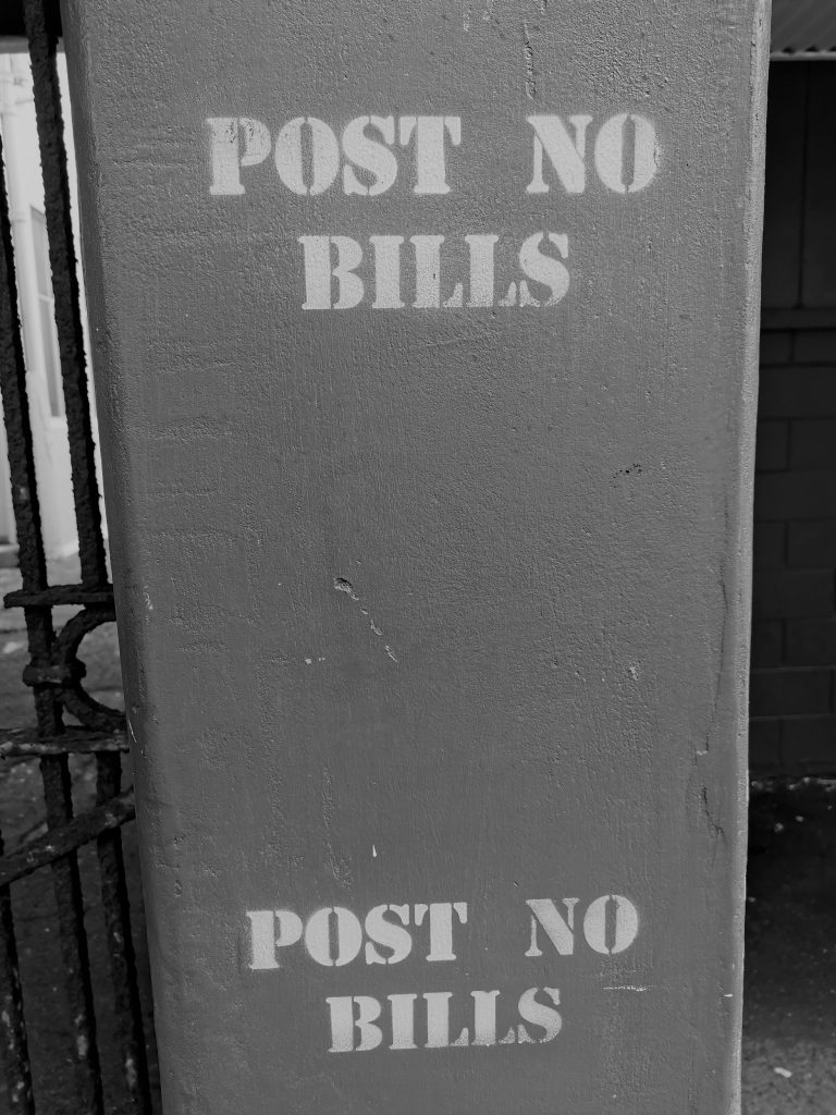 the instruction to Post No Bills is stencilled on a concrete pillar