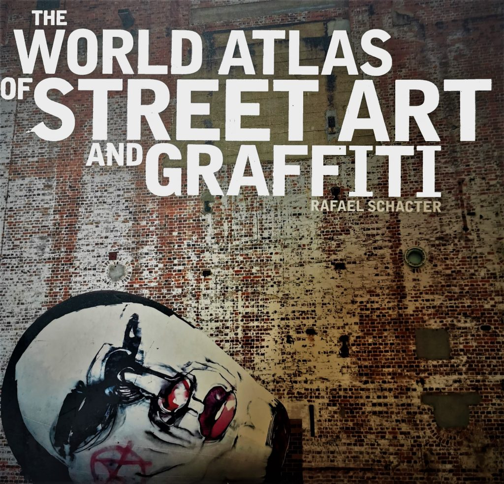 The cover of the book The World Atlas of Street Art and Graffiti, featuring a painting by Anthony Lister on a brick wall