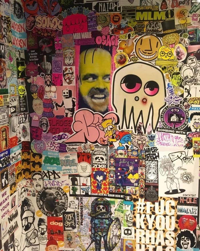 A wall covered in stickers at a sticker fest.