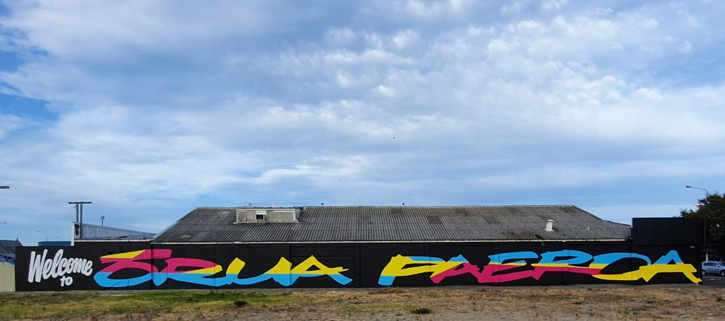 A long block wall is painted black, with the words Welcome to Orua Paeroa painted in bright colours.