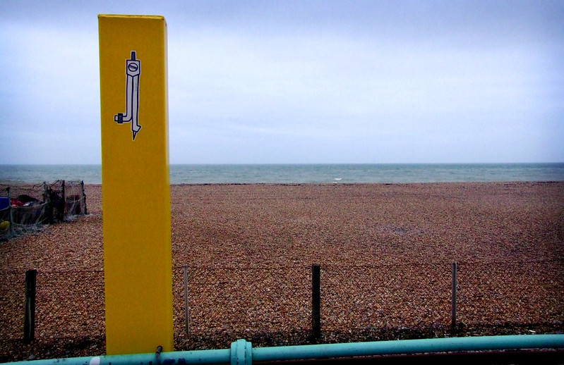 A small Teeth Like Screwdrivers compass sticker on a yellow pole on the beach, Brighton, United Kingdom (photo credit: Butterstotch)