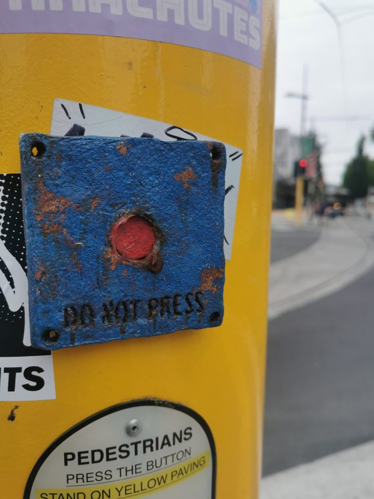 One of Mike Beer's 'Do Not Press' buttons applied to central Christchurch streets. When passersby could not follow the advice, and pressed the button, sriracha sauce oozed out...