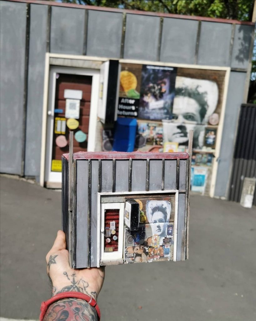 The artist holds his scratch build of the original home of Lyttelton's Dead Video in front of the real thing