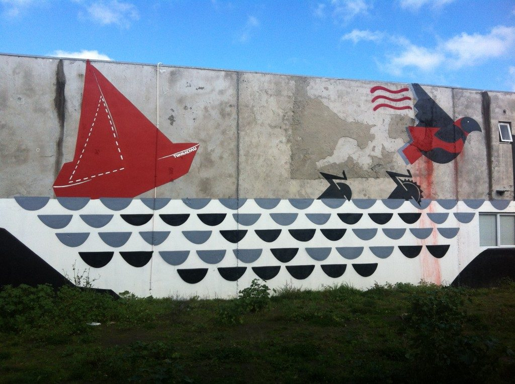 Work's mural for From the Ground Up in 2013. The image in red, black, grey and white, features figures escaping from a ship wreck with a bird flying above them.