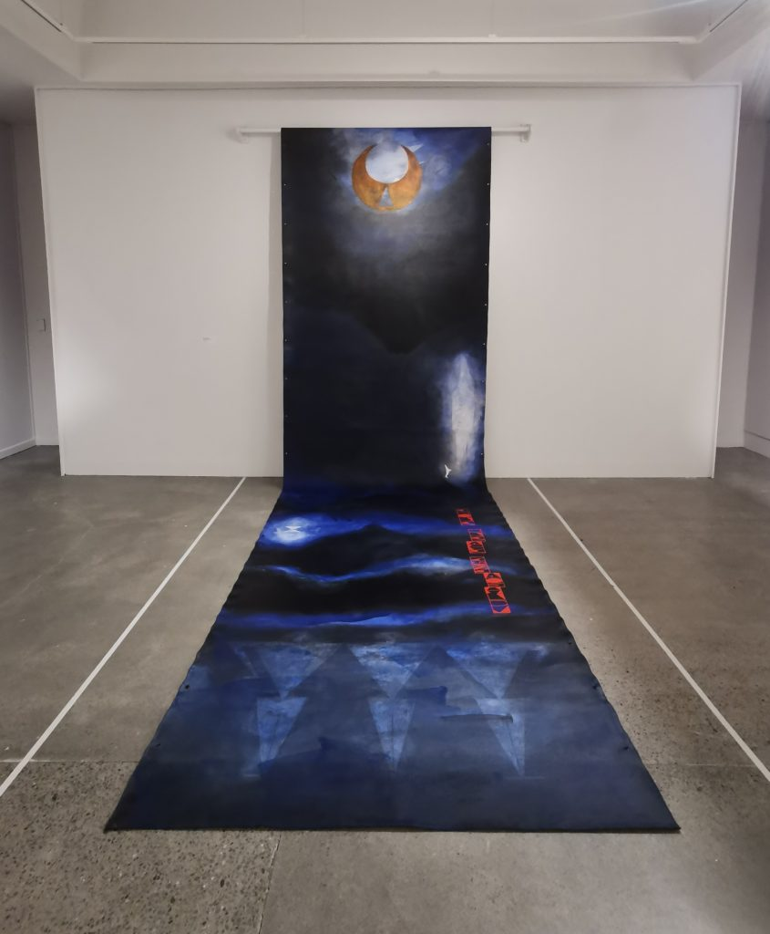 Work's piece for the TMD: An Aotearoa Graffiti Story at Lower Hutt's Dowse Art Gallery. The unfurling piece is dark blue and depicts a moon glowing at the top of the section on the wall, there are figures on the section rolled along the floor.